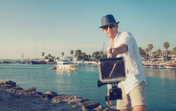 Den stiliga mannen med handlingkameran tar ett selfiefoto i tropien royaltyfria foton