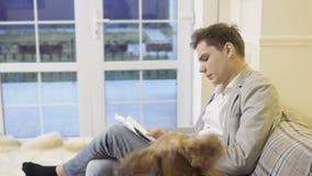 Den stiliga mannen med hunden sitter på soffan arkivfilmer