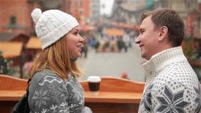 Den stiliga mannen och den härliga kvinnaanseendeframsidan - till - framsidan med koppen kaffe på jul marknadsför bakgrund förbun lager videofilmer