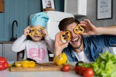 Den stiliga mannen och hans lilla gulliga dotter lagar mat på kök framställning av sallad sund livsstil för begrepp arkivbild