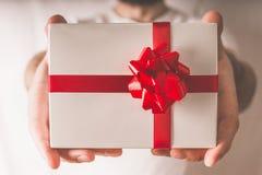 Den stiliga mannen räcker den hållande gåvaasken med det röda bandet, slut upp royaltyfri bild