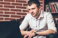 Den stiliga mannen ser bärbar datorskärmen på bakgrund av kontorskabinettet Han är iklädd affärsdräkten i svartvitt Co arkivfoton