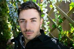 Den stiliga mannen som bär den svarta skjortan med blåa ögon och skägget, ser in i kamera royaltyfria bilder
