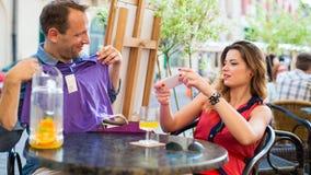 Den stiliga mannen som försöker på t-skjortan i kafé, sitter han med hans flickvän. Arkivbild
