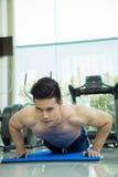 Den stiliga mannen som kondition som övar, genom att göra, skjuter, ups som delen av bodybuildingutbildning i konditionmitten, sp Royaltyfri Fotografi