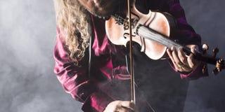 Den stiliga mannen som spelar den klassiska fiolen i blått, röker Royaltyfri Fotografi