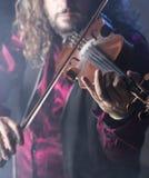 Den stiliga mannen som spelar den klassiska fiolen i blått, röker Arkivbild