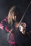 Den stiliga mannen som spelar den klassiska fiolen i blått, röker Royaltyfria Foton