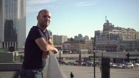 Den stiliga mannen står på den stads- balkongen arkivfilmer