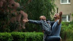 Den stiliga mannen svänger hans flickvän på armarna under en regnig dag i staden parkerar Barnpar som tycker om regnet stock video