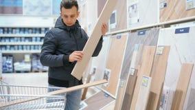 Den stiliga mannen väljer, och köpande byggnadsmaterial i konstruktion shoppar lager videofilmer