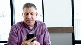 Den stiliga mellersta åldriga mannen i tillfällig kläder använder en smart mobil mobiltelefon och ler, medan sitta nära fönstret arkivfilmer