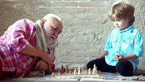 Den stiliga morfadern och sonsonen spelar schack, medan spendera tid tillsammans hemma Pys som spelar schack med hans stock video