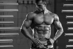 Den stiliga muskulösa manvisningen tränga sig in och att posera i idrottshall Stark manlig torsoabs, genomkörare arkivfoto