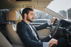 Den stiliga och säkra unga mannen sitter i bil och ser rättfram Han kör bilen Det ser lyxigt inom Han rymmer arkivfoto
