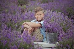 Den stiliga pojken med blonda hår som bär den blåa tshirten och stilfulla kortslutningar med blockgalge som poserar på sommar, sä fotografering för bildbyråer