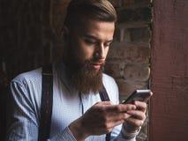 Den stiliga rikeman använder en telefon Royaltyfria Foton