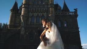 Den stiliga romantiska brudgummen och härliga blonda bruden som poserar nära den gamla väggen, rockerar arkivfilmer