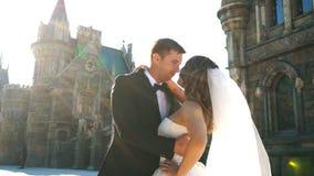 Den stiliga romantiska brudgummen och härliga blonda bruden som poserar nära den gamla väggen, rockerar stock video