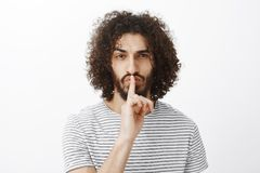 Den stiliga säkra manliga coworkeren i stilfull randig t-skjorta och att göra shh gesten som säger hyssjar ner med pekfingret öve Royaltyfria Bilder