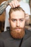 Den stiliga skäggiga grabben deltar i frisören fotografering för bildbyråer