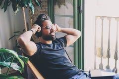 Den stiliga skäggiga mannen i hörlurar tycker om att lyssna till musik hemma Koppla av och vilotidbegrepp suddighet bakgrund Arkivfoto