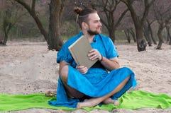 Den stiliga skäggiga mannen med utgör, bullen på huvudet i blått kimonosammanträde som rymmer den stängda boken arkivfoto