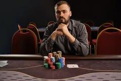 Den stiliga skäggiga mannen spelar poker som sitter på tabellen i kasino royaltyfria foton