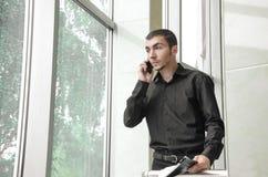 Den stiliga unga affärsmannen rymmer legitimationshandlingar med plan och talar på mobiltelefonen som står i kontoret royaltyfri bild