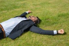 Den stiliga unga affärsmannen som ligger på gräs med armar, öppnar royaltyfri fotografi