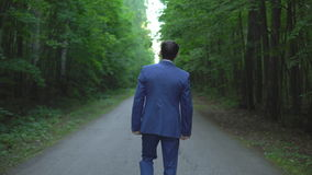 Den stiliga unga affärsmannen som promenerar vägen i skog, beskådar tillbaka lager videofilmer