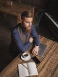 Den stiliga unga affärsmannen vilar i kafé fotografering för bildbyråer