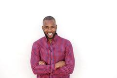 Den stiliga unga afrikanska mannen som ler med armar, korsade vid den vita väggen arkivbild