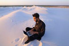 Den stiliga unga arabiska mannen skriver på internet genom att använda bärbara datorn och sitter Royaltyfri Foto