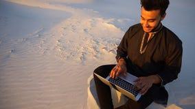 Den stiliga unga arabiska mannen skriver på internet genom att använda bärbara datorn och sitter på sand under sandig öken på sol lager videofilmer