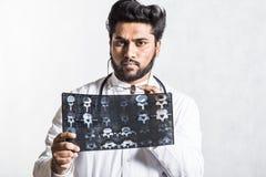 Den stiliga unga doktorn i ett vitt lag med en stetoskop kontrollerar uppm?rksamt patientens r?ntgenstr?le arkivfoton