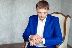 Den stiliga unga eleganta mannen i dräkten som kopplar av, sitter på armstol fotografering för bildbyråer