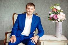 Den stiliga unga eleganta mannen i dräkten som kopplar av, sitter på armstol royaltyfria foton