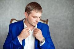 Den stiliga unga eleganta mannen i dräkten som kopplar av, sitter på armstol Arkivfoto