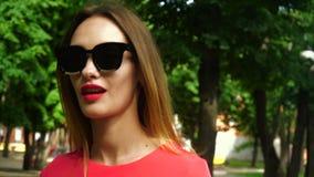 Den stiliga unga kvinnan i solglasögon med röda kanter går utomhus lager videofilmer