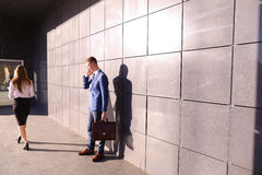 Den stiliga unga mannen, affärsmannen som talar på telefonen, förbigår beaut royaltyfria foton