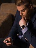 Den stiliga unga mannen använder en telefon Royaltyfri Bild