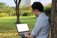 Den stiliga unga mannen arbetar med bärbar datordatoren för hans arbete i stad parkerar royaltyfri fotografi