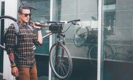 Den stiliga unga mannen Ciyclist med exponeringsglas bär cykeln på hans dagliga rutinmässiga livsstil för skuldragatan royaltyfria foton