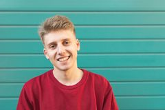 Den stiliga unga mannen i en röd tröja mot en turkosvägg ser kameran och leendena fotografering för bildbyråer