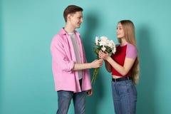 Den stiliga unga mannen i rosa skjorta ger en bukett av vita blommor till hans h?rliga blonda flickv?n arkivfoton