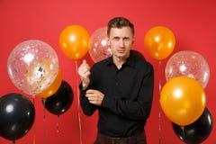 Den stiliga unga mannen i svart klassisk skjorta rätar ut manschetter som firar på röda bakgrundsluftballonger St-valentin` s arkivfoto