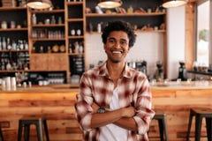 Den stiliga unga mannen med hans armar korsade i ett kafé arkivbild