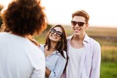 Den stiliga unga mannen och den härliga unga kvinnan står i fältet med vänner och att skratta fotografering för bildbyråer