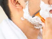 Den stiliga unga mannen rakar hans framsida Begrepp för livstil arkivfoto